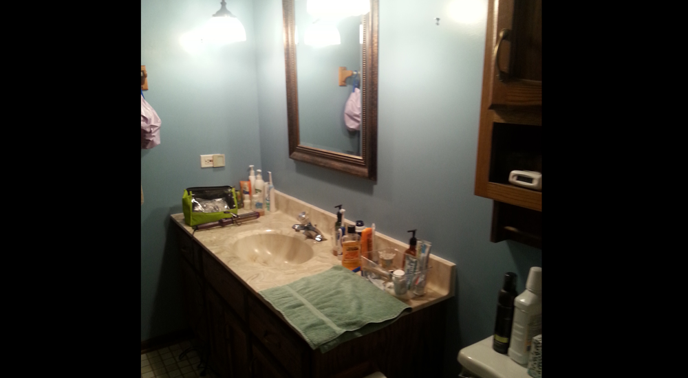 Small mirror and cluttered countertop