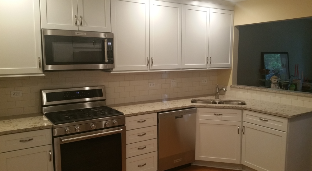 White cabinets and stainless steel appliances for a modern look. Microwave is added above the stove.