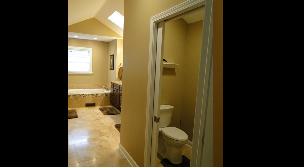 The commode area is now to the front of the bathroom, leaving bathing and showering to the back